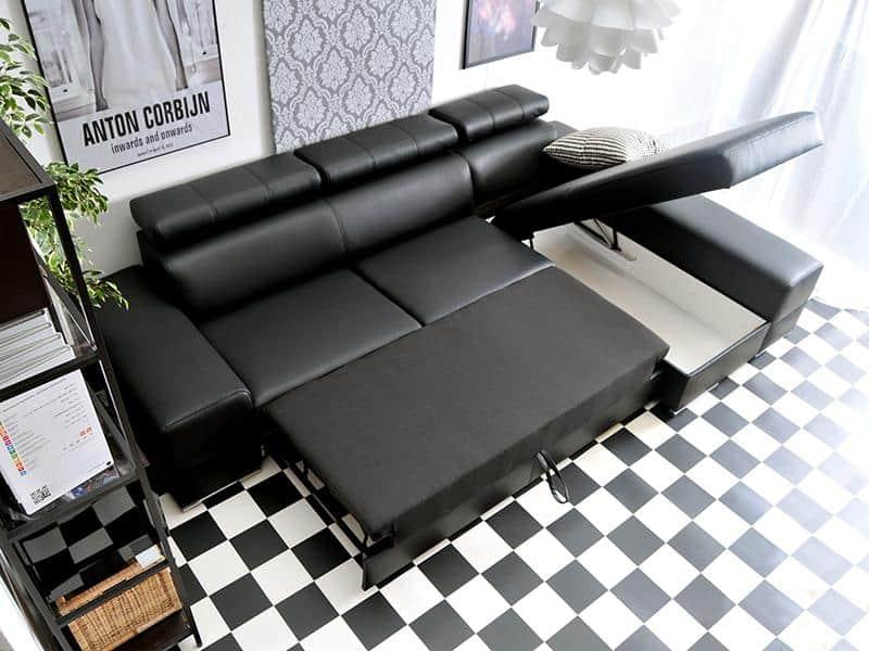 Ashley sovesofa med chaiselong udført i sort stof vist med åben opbevaring samt omdannet til seng
